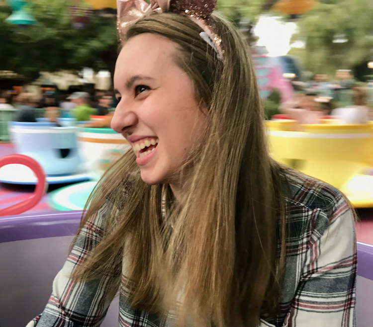 Girl with Mickey Mouse ears on Teacup ride at Disneyland.