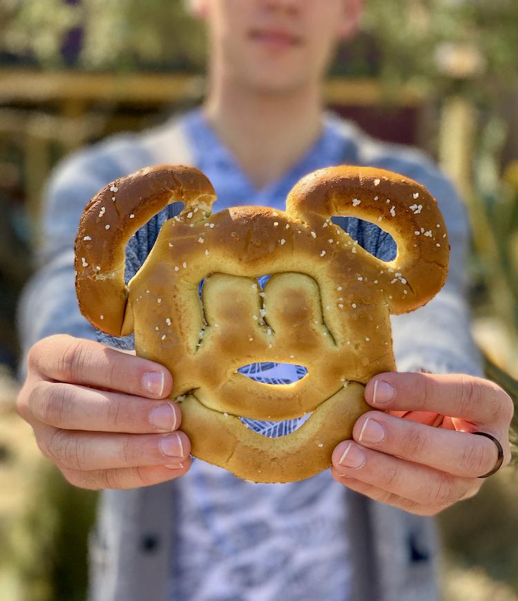 boy holding a mickey mouse pretzel