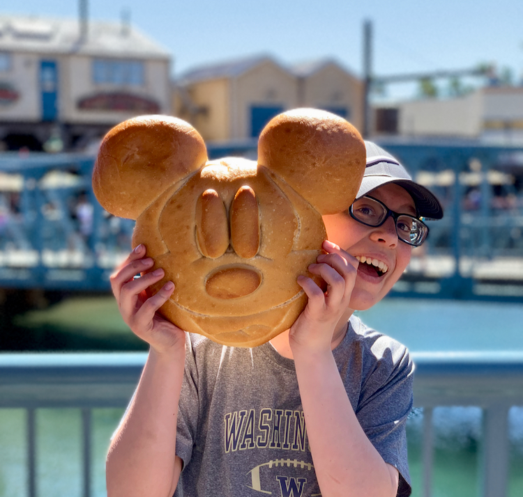 boy holding large loaf of sourdough bread shaped like mickey mouse