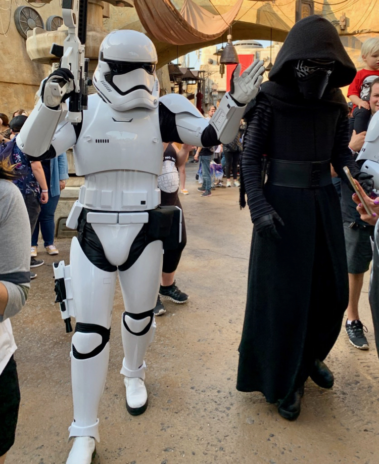 kylo ren and a storm trooper walk the streets of batuu
