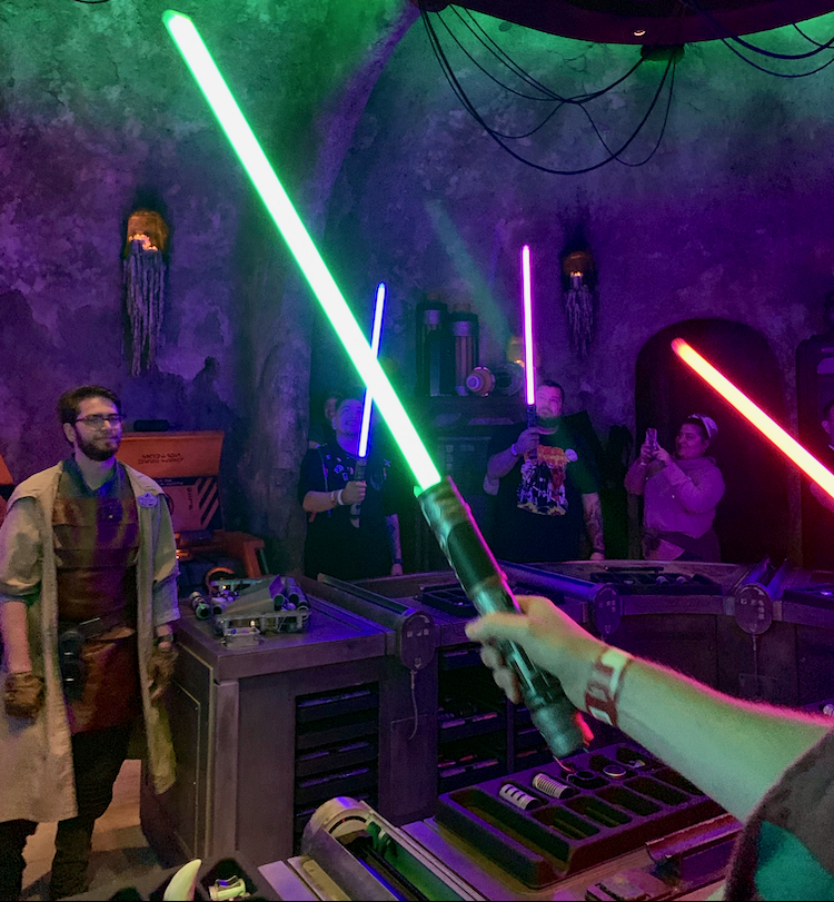 a room full of people with new lightsabers