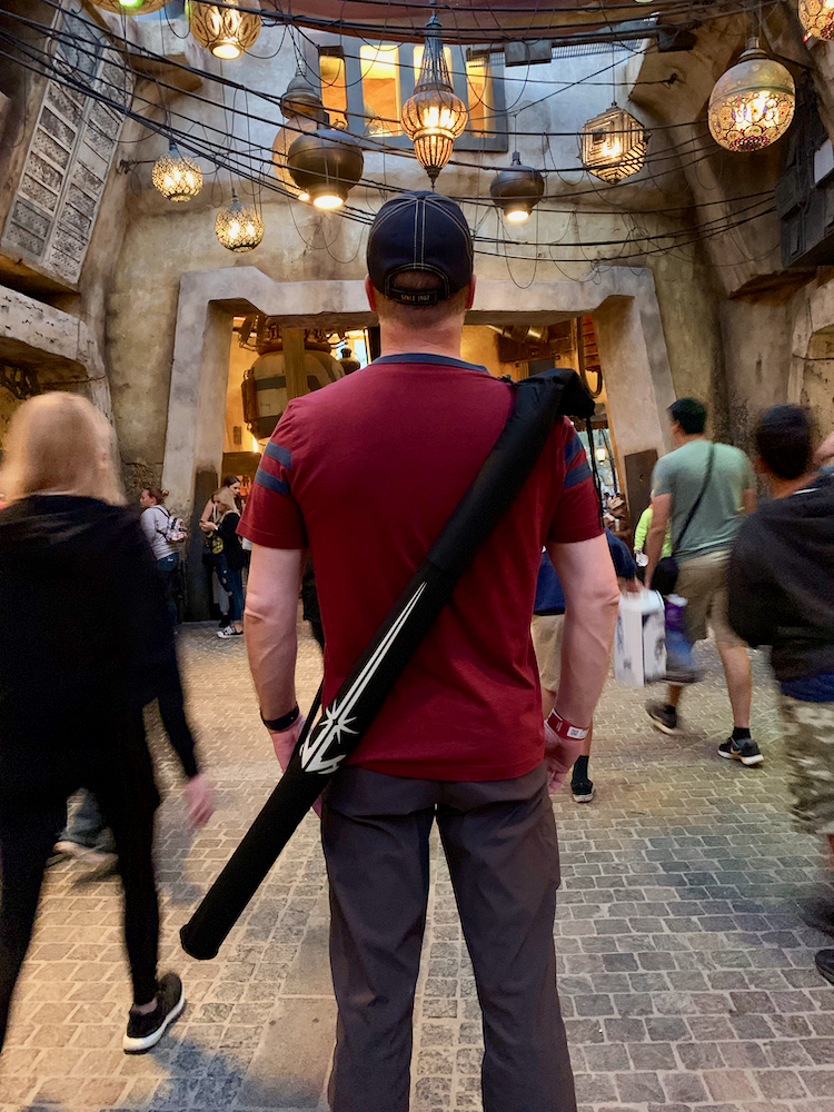man with lightsaber carrying case slung over his shoulder